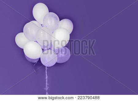 holidays, birthday, party and decoration concept - close up of inflated white helium balloons on ultra violet background