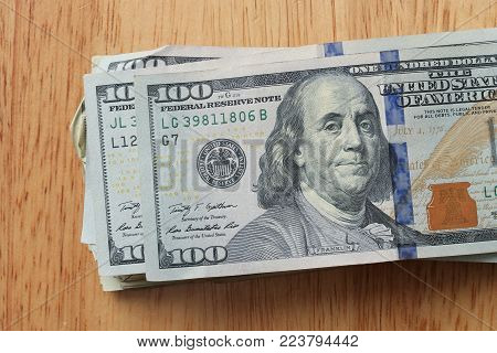 stack of Hundreds Dollars bills on wood surface