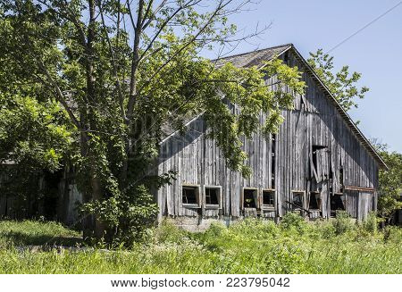 A decaying wooden barn in a rural area.