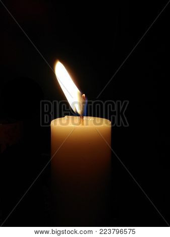 One candle light in the dark. Burning candle with dark background. a candle flame. the only one fired candle on black background. a candle fire.