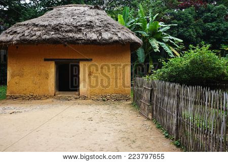 Rustic adobe building with wooden fence and packed dirt yard in rural Southeast Asia