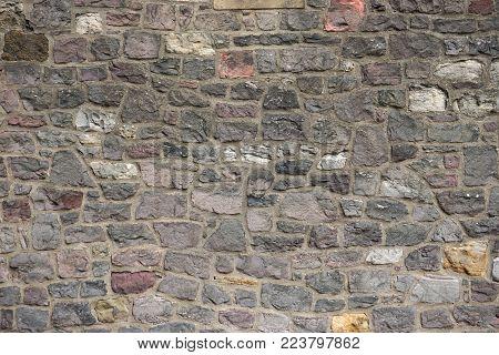 Ancient stone wall with irregular blocks set in mortar horizontal background