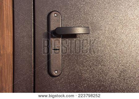 door handle. close up. dark door. the door is closed.