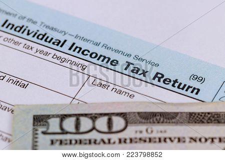 Tax time - Closeup of U.S. 1040 tax return with 100 bills pay tax
