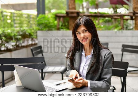 Business Concept.Young Asian businesswoman is working happily.Young businesswoman working in a cafe.Young businesswoman is relaxation in a coffee shop.