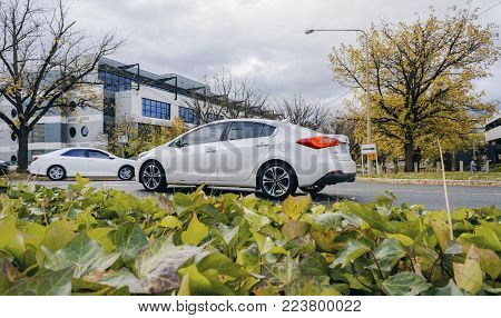 Canberra, Australia - Apr 26, 2017: Autumn day scene at the intersection of National Circuit and Bourke Street. Dramatic clouds with a car waiting to make a turn.