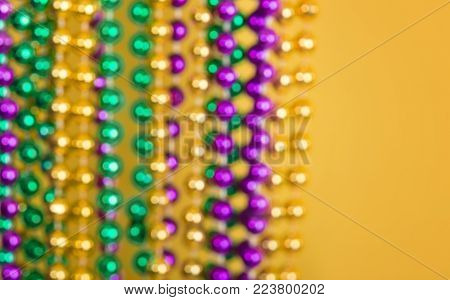 Defocused Mardi Gras beads against golden yellow background with copy space