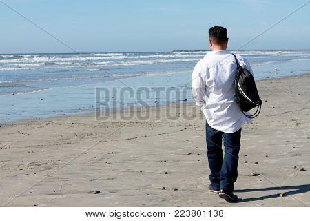 Unidentified man walking on the beach