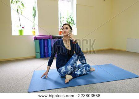 Beautiful girl check correctness of sun salutation on laptop. Lady strengthens all body major muscle groups in surya namaskar. Concept of online tutorial, using advanced technologies.