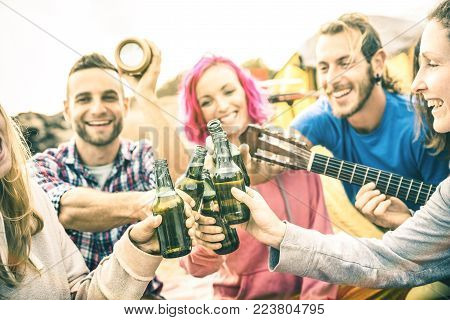 Young friends having fun together at beach camping party - Friendship travel concept with hipster people wanderers playing guitar and drinking bottled beer at summer surf camp
