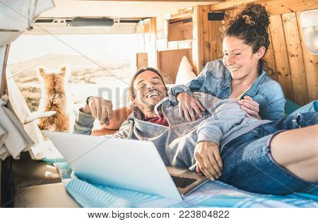 Hipster couple with dog traveling together on retro mini van transport - Life inspiration concept with indie people on minivan adventure trip watching laptop pc in relax moment