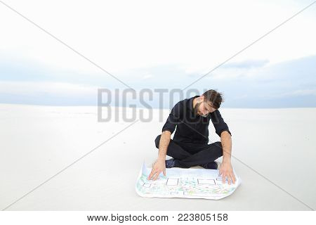 constructor talk on smartphone, bearded fellow waiting for friend to work on project of waste processing plant in countryside. Young fair-haired man wearing black shirt trousers sitting on sand holding whatman paper.