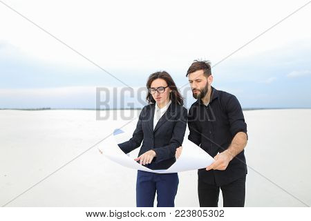 designer man and representative of investment company woman holding whatman paper with plan, people discussing spa-center in countryside. Bearded fair-haired guy and female in glasses smiling talking about project.