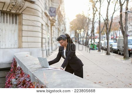 Young businesswoman working with laptop near high building on balcony. Young female person working with color diagram on paper. Concept of making plan for biz using modern technologies and good Internet.