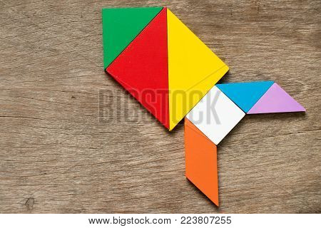 Colorful tangram puzzle in rocket or missile shape on wood background