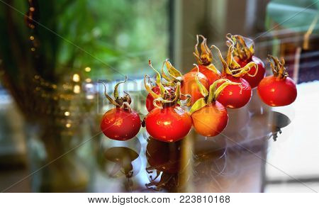 Rose hips from Rosa rugosa on a glass. Close up.