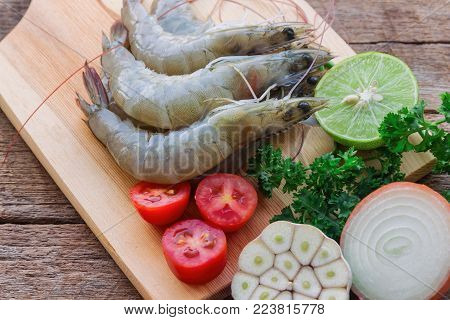 Fresh white shrimps on wood cutting board in close up view. Prepared raw prawn or shrimps and vegetable and herbs for cooking. Fresh shrimp for cook seafood menu on wooden table. Homemade delicious food concept. Fresh shrimp prepared for cooking.