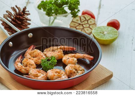 Grilled shrimp with spice. Fried prawn or shrimps served on red fried pan on white wood table with copy space. Delicious prawn steak for special lunch or dinner. Homemade food of shrimps for seafood grilled menu. Grilled shrimp ready to served.