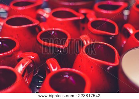 a lot of clean empty red mugs on the bar.