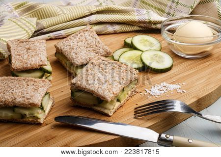 dark toast slices with cucumber and coarse salt on a wooden board