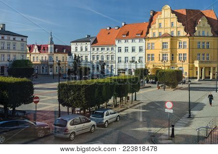 BIALOGARD, WEST POMERANIAN / POLAND - 2015: Cars and people on sunny square of the town hall provincial town