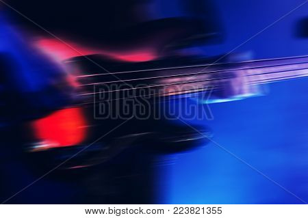 Blurred rock music background, bass guitar player on a stage with blue illumination