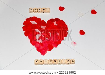Happy Valentine written with white cubes with black letters beside a bigger red heart made with smaller red hearts