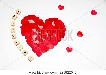 white cubes with black letters beside a bigger red heart made of smaller red hearts on a white background
