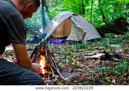 Tourist Tents On The Edge Of The Forest. A Bright Fire Brightens The Room. Travel Of Tourists To Nat