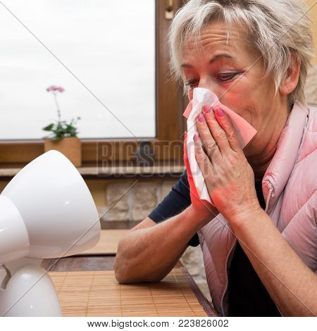female senior adult with handkerchief, is having flu. infrared light points to her face