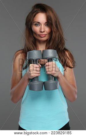Attractive slim woman in azure sportswear holding pair of dumbell. Isolated on grey background.
