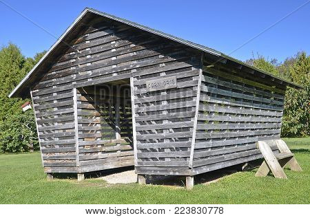Well preserved old air dried drive through  wood corn crib.