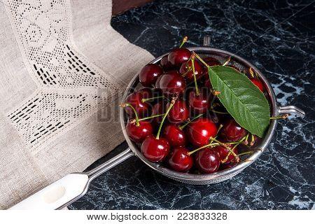 Fresh Organic Sweet Cherry And Big Green Leaf In Steel Colander On Dark Marble Background.