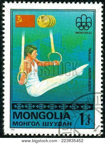 Ukraine - circa 2018: A postage stamp printed in Mongolia show gymnast Nikolai Andrianov and USSR flag. Series: Medalists from Montreal. Circa 1976