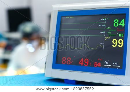 Electrocardiogram in hospital surgery operating emergency room showing patient heart rate with blur team of surgeon background