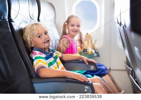 Child in airplane. Kids sit in air plane window seat. Flight entertainment for kid. Traveling with young children. Kids fly and travel. Family summer vacation. Girl and boy with toy in airplane.