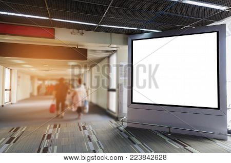 mock up of vertical advertising billboard or big blank showcase light box for your text message or media content with people walking at the airport, commercial, marketing and advertisement concept