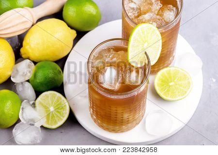 Glass of Tsasty Ice Tea with Ice Cubes and Citrus Cold Summ er Beverage Wooden Squeezer and Raw Lemons and Limes on Background Above