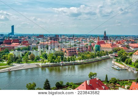 Wroclaw/Poland- August 18, 2017: aerial panoramic cityscape of river Odra with touristic boat, historical and modern buildings, summertime, blue sky