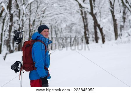 Adventurer with snowboard and backpack stands in the forest after snowfall, meditating and admiring snow covered trees on the slope - anticipation of adventure. Blurred background.