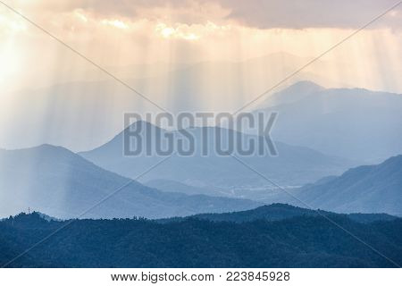 Sunbeam from cloudy sky shining through fog to blue complex mountains range in morning after very cold night of winter season.