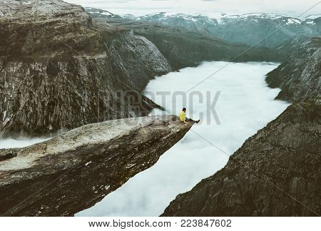 Man traveler on Trolltunga rocky cliff edge in Norway mountains Travel Lifestyle adventure emotional concept extreme vacations outdoor above clouds tourist sitting alone
