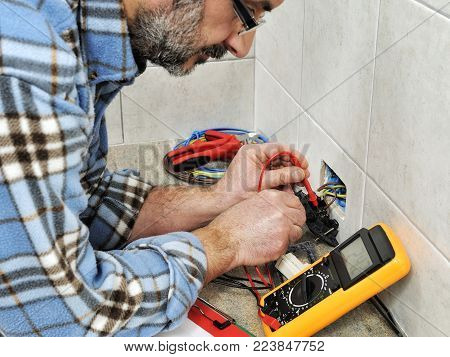 Electrician technician at work measures the voltage of a residential electrical system.