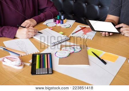 Two professional stylish fashion designer working as fashion designers measure as sketches in workshop of new collection in art, Creative Design and Artistic Concept.