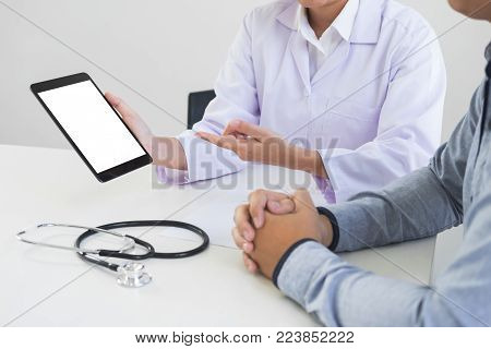 Professor Doctor presenting report and recommend a method with patient treatment on digital tablet while sitting at table.