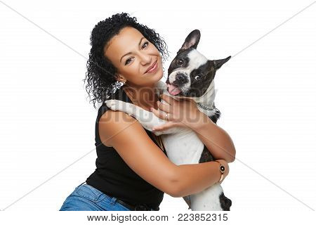 beautiful young woman holding french bulldog dog. studio shot isolated on white background. copy space.