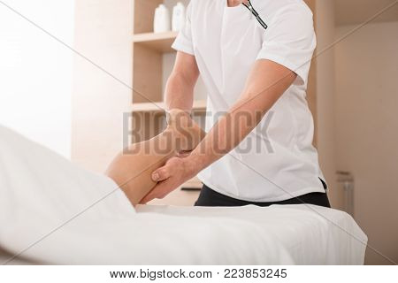 Masseur giving adult female a massage. Therapist massaging the leg of lady while she is lying on the couch. Close up