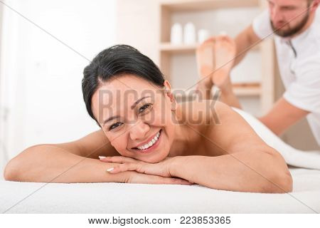 Portrait of cheerful middle-aged woman taking procedure at spa. She is lying on massage table and smiling while looking at camera
