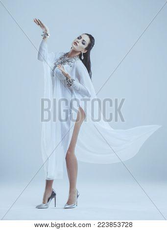 Sensual oriental belly dancer dancing in studio, grey background, cinematic style