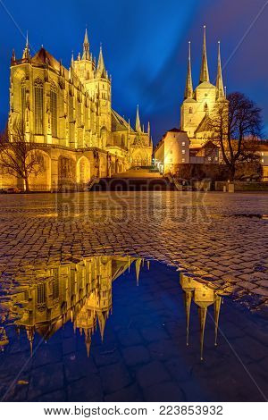 The Famous Cathedral And Severi Church In Erfurt At Dusk Reflected In A Puddle